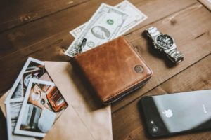 There is a wallet, money and a clock on the desk