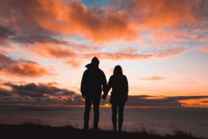 A couple is holding hands against the sunset