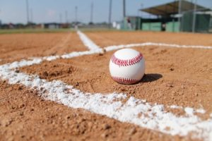 A baseball ball is rolling on the ground