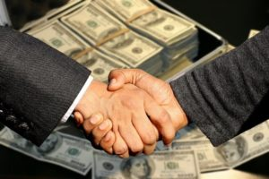 Shaking hands in front of money