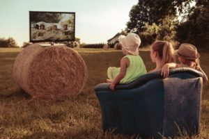 Family watching TV on grassland