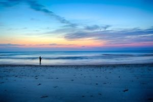 A man is fishing on the beach watching the sunrise