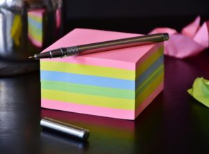 A pen is on many sticky notes