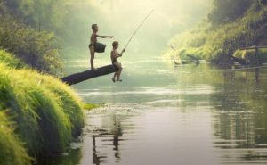 Two children are fishing in the river