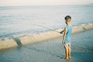 The child is fishing in the sea