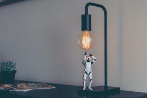 The robot is trying to touch the light bulb