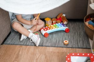 A child is playing with a toy xylophone
