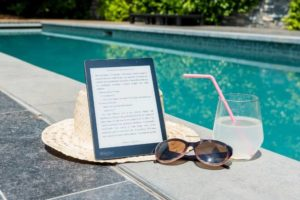 There is a straw hat and an e-book in the pool