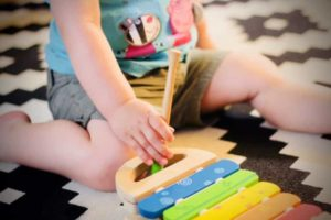 A child is playing with a xylophone toy
