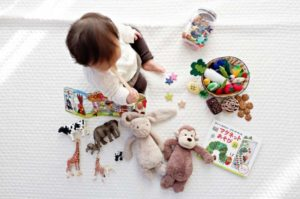 A child surrounded by many toys